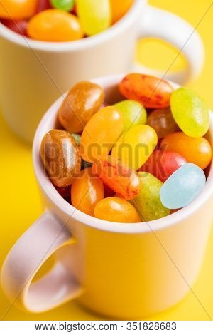 Fruity jellybeans. Tasty colorful jelly beans in cup on yellow background.