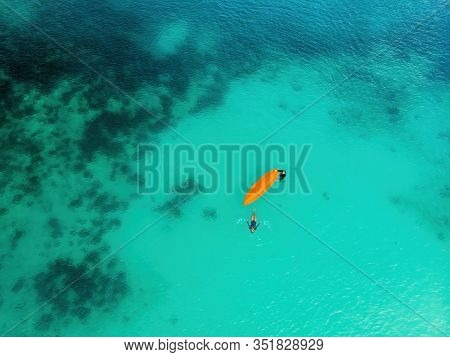 Man And A Woman With A Kayak In The Sea With Clear Turquoise Water. Kayaking, Leisure Activities On