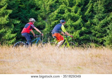 Cyclist Riding Near Hay And Pine Trees Through The Mountain Path