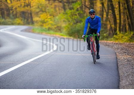Young Well Equipped Man Standing With His Racing Bike By The Roadside