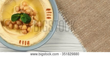 Panoramic Shot Of Hummus Dish On Hessian Sack And Wooden Surface