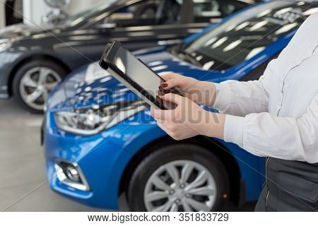 Woman Dealer Using Digital Tablet At Dealer Showroom. Touching Screen Digital Tablet. Modern Working