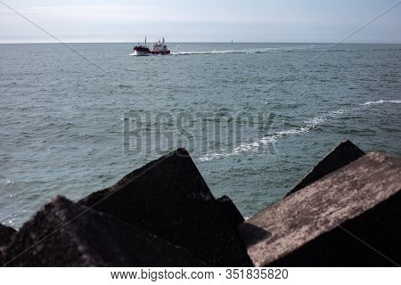View From Afar Of Nave Ship On The Sea, On The Background Of Blue Sky And A Lighthouse.