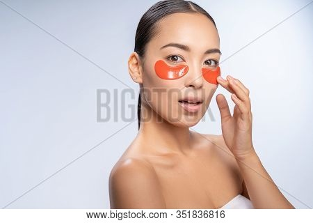 Emotional Brunette Woman Putting Eyepatches On Face