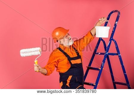 Working In Repair Shop. Senior Man Painter Use Roller On Ladder. Painting The Wall In Pink. Professi