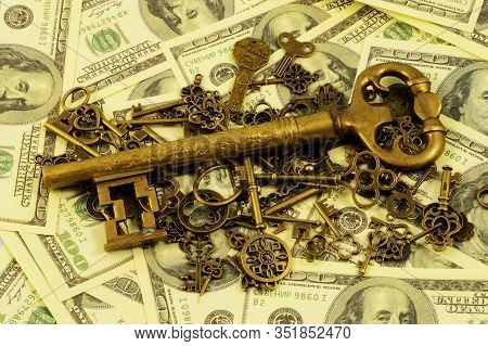 A Pile Of Brass Keys With A Larger Dominant One Centered On A Background Of American Hundred Dollar