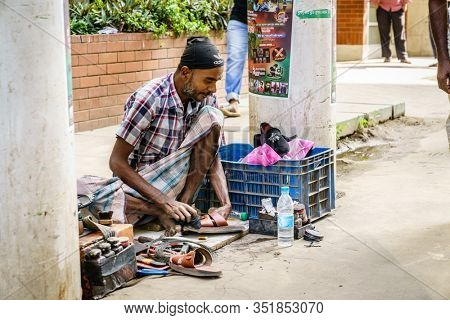 Chittagong, Bangladesh, December 22, 2017: shoe repair service on a street of Chittagong in Bangladesh