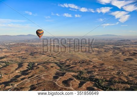 Hot air balloons fly over the grape vineyards in Temecula, California.  This is a popular tourist attraction in this vacation tourism area.