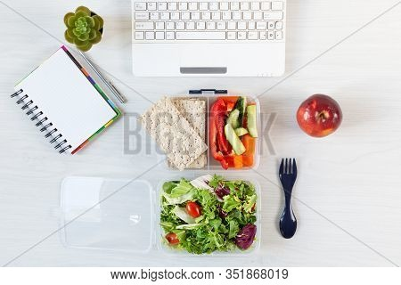 Vegetables And Fresh Green Salad In Lunch Box On Working Desk With Laptop And Other Office Supplies.