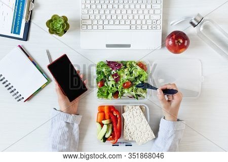 Hands Of Business Woman Working On Phone And Eating Healthy Business Lunch At Workplace. Vegetables
