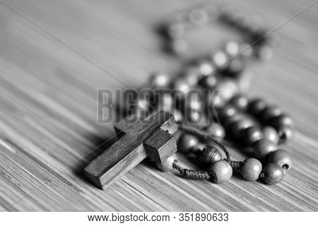 Rosary Beads And Jesus Christ Crucifix Holy Cross With Copy Space  In Black And White Background.