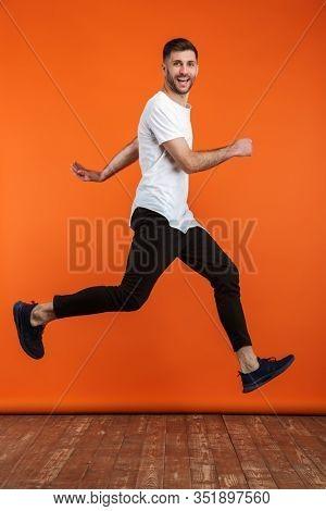 Image of young bearded man wearing basic white t-shirt running isolated over orange background