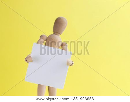 Wooden Mannequin Holds In Hand A Blank Bulletin Board. Wooden Dummy Presents Your Business. Copy Spa