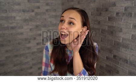 A Beautiful Emotional Woman In A Plaid Shirt Is Holding Hand At Her Ear And Trying To Overhear Conve