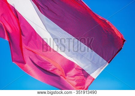 National Flag Of Latvia Against Blue Sky. Wind Is Waving Red And White Flag. National Symbol Of The