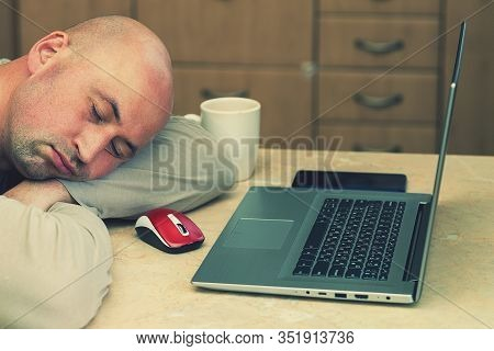 Man Sleeping On The Table With Laptop At Home. Bald Man Sleeping At His Working Place Home Office. P