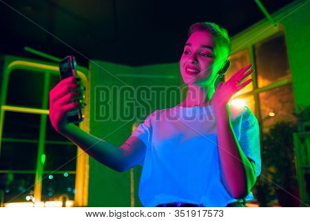 Greeting. Cinematic Portrait Of Stylish Woman In Neon Lighted Interior. Toned Like Cinema Effects, B