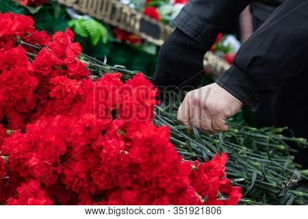 Red Carnations Are Laid On The Marble Memorial In Honor Of Those Killed In The War