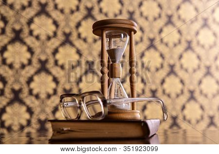 Hourglass, Old Book And Eyeglasses On Wooden Table, Pattern Background. Sand Falling Down Inside Of