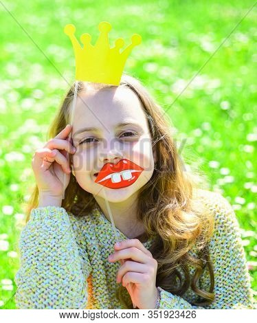 Girl Sits On Grass At Grassplot, Green Background. Sweet Little Girl With Crown, Outdoor Photo. Humo