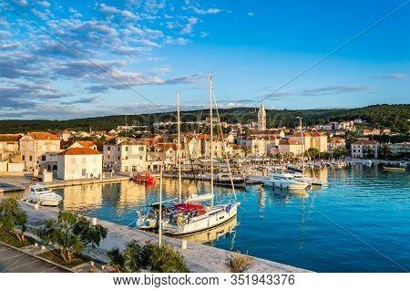 Supetar On Brac Island Near Split, Croatia. Small Seaside Town With Promenade And Harbor With White