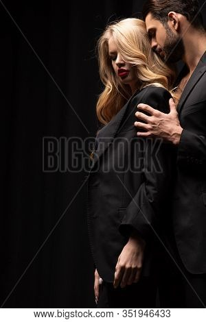 Handsome Man Touching Beautiful Woman In Suit Isolated On Black