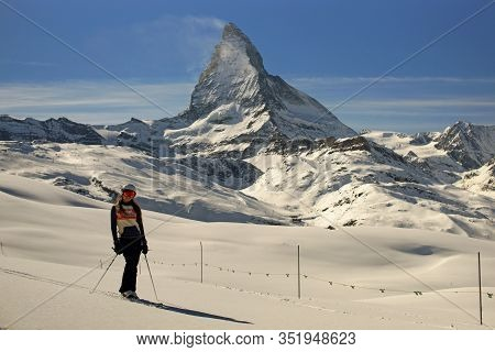 Young Woman On Ski In Ski Helmet And Mask Standing On Untouched Snow Near Matterhorn Mountain, Freer