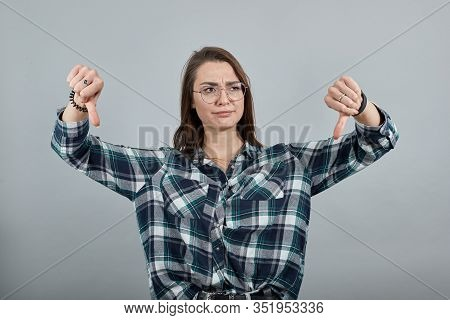 Young Brunette Girl Blue Green In Checked Shirt On Grey Background Dissatisfied Protest Woman In Gla