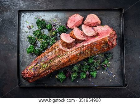 Barbecue dry aged venison tenderloin fillet steak and saddle natural with offered as top view on a rustic board
