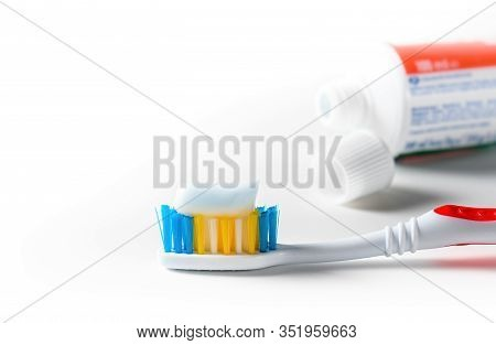 Toothbrush With White Toothpaste And Tube Of Toothpaste Over White Background. Close-up.