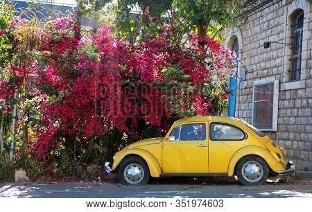 Nazaret, Israel - 14 June 2019: Yellow Volkswagen Beetle Vintage Car Parked In A Street Near Pink Bl