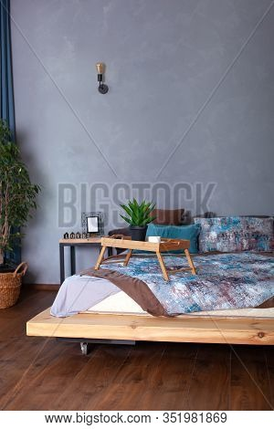 Bedroom Interior With A Small Table On Bed And A Cup Of Coffee. Wooden Breakfast Tray On Bed In Morn