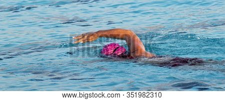Horizontal View Of A Female Swimmer Swimming With A Freestyle Stroke In An Outdoor Pool Training For