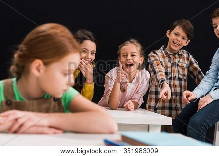 Selective Focus Of Classmates Laughing And Pointing With Fingers At Schoolgirl Isolated On Black, Bu