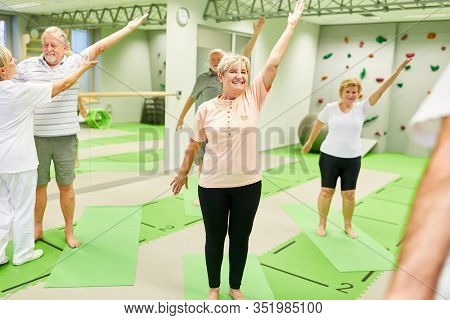 Seniors enjoy back exercises in a rehabilitation course with a physiotherapist