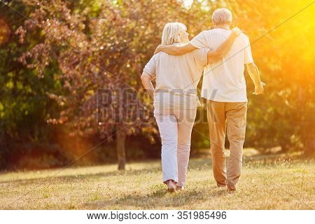 Two seniors go for a walk in nature in summer