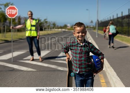 Portrait of a Caucasian schoolboy standing by the road holding a skateboard and a helmet and smiling to camera, a Caucasian woman wearing a high visibility vest and holding a stop sign standing in the