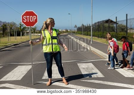 Front view of a blonde Caucasian woman wearing a high visibility vest and holding a stop sign, standing in the road, turning to face a diverse group of schoolchildren on a pedestrian crossing,