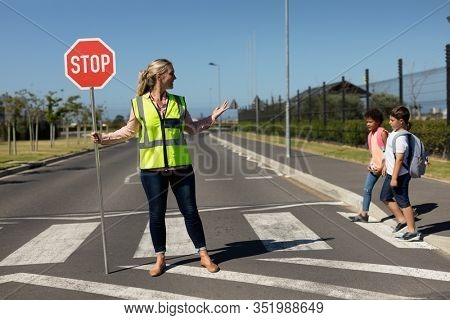 Front view of a blonde Caucasian woman wearing a high visibility vest and holding a stop sign, standing in the road, turning and smiling to two schoolchildren on a pedestrian crossing, stopping the