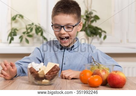 The Boy In Glasses Sits At The Table And Stares At The Sweets With A Happy Expression. Next To It Li