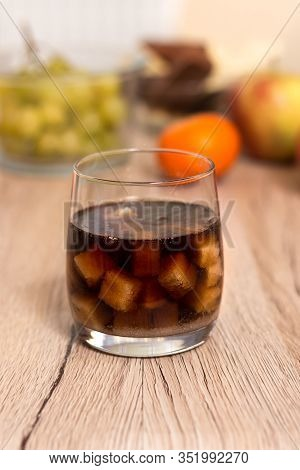 A Glass Filled With Sugar Cubes Flooded With Cola Stands On The Kitchen Counter. In The Background O