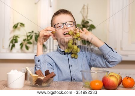 Smiling Boy Sits At The Table And Eats Fruit. He Has Grape Fruit In His Teeth.