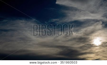 Dark And Dramatic Storm Clouds At Sunset With A Jet Contrail Through The Middle Of The Sky