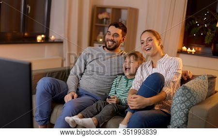 family, leisure and people concept - happy smiling father, mother and little son with remote control watching something funny on tv at home at night