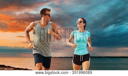 fitness, sport and healthy lifestyle concept - happy couple in sports clothes and sunglasses running over sea and sunset sky background