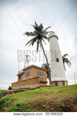Old Lighthouse Building And High Coconut Palm Tree On The Tropical Island