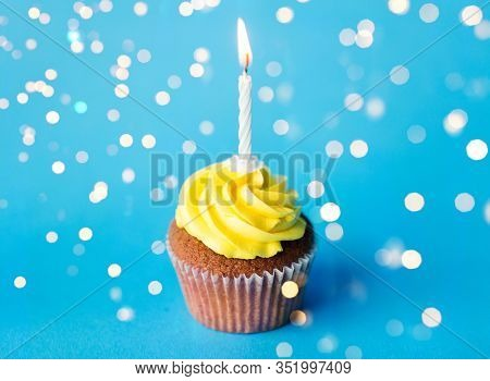 holiday, celebration, greeting and party concept - birthday cupcake with yellow buttercream frosting and one burning candle over festive lights on blue background