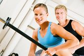 Very attractive and sportive couple doing power gymnastics with barbells poster
