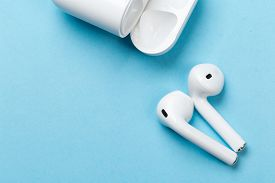 White Wireless Headphones With Microphone On A Blue Background With Charger Background