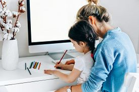 Rear View Image Of Young Woman With Daughter Sitting At Home And Working. Young Mother With Toddler